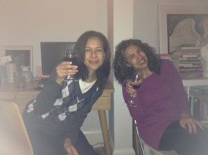 Ladies sipping on a warming red by the candle light.