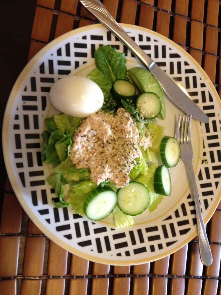 Green salad topped with tuna, a hard boiled egg.
